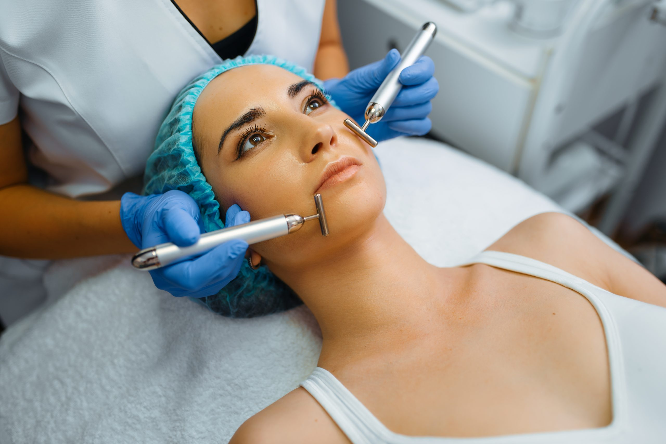 Cosmetician smoothes face of female patient